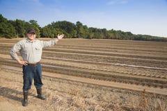 Granjero que muestra su tierra de cultivo Imagen de archivo
