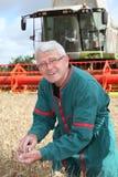 Granjero que se coloca en campo de trigo Foto de archivo libre de regalías