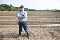 Granjero que se coloca en tierra de cultivo Fotos de archivo