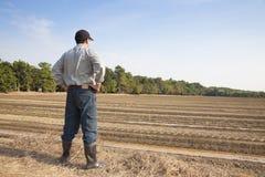 Granjero que se coloca en tierra de cultivo Imágenes de archivo libres de regalías