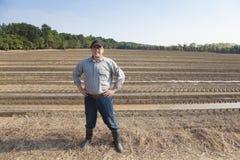 Granjero que se coloca en tierra de cultivo Foto de archivo libre de regalías