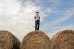 Granjero que se coloca en una bala de heno enorme debajo de un cielo del verano Imagen de archivo