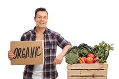 Granjero que se inclina en un cajón por completo de verduras Imágenes de archivo libres de regalías