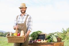 Granjero que sostiene la cesta de verduras en el mercado Imagen de archivo