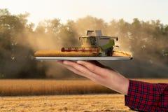 Granjero que sostiene una tableta con una m?quina segadora imagen de archivo libre de regalías