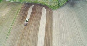Granjero que trabaja en campo de trigo Tractor que ara el campo agrícola almacen de metraje de vídeo