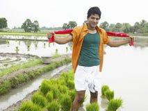Granjero que trabaja en su campo de arroz Imagenes de archivo