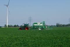 Granjero que trabaja los campos en primavera adem?s de las turbinas de viento enormes imagen de archivo