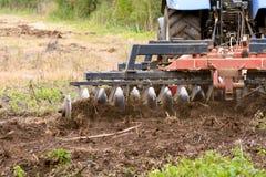 Granjero que usa el tractor para arar el campo Imagenes de archivo