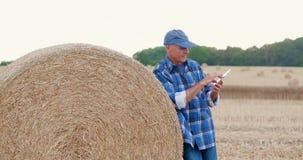 Granjero que usa la tableta digital mientras que hace una pausa la bala de heno almacen de video
