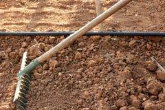 Granjero que usa un rastrillo para nivelar el suelo marrón en el jardín imagen de archivo libre de regalías