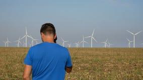 Granjero que va en su campo hacia las turbinas de viento y que habla en el teléfono móvil Producción de electricidad, energía ver metrajes