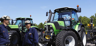 Granjero y mecánico con los tractores grandes imagen de archivo