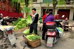 Pengzhou, China: Granjeros que pesan verdes del ajo Foto de archivo