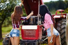 Granjeros de sexo femenino atractivos que fijan el tractor Fotografía de archivo