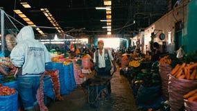 granjeros locales que venden su producción que la ciudad comercializa con un hombre con una carretilla foto de archivo libre de regalías