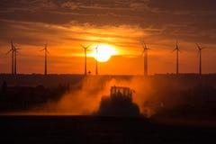 Granjeros que trabajan con un tractor en el campo en la puesta del sol con las turbinas de viento en el fondo Foto de archivo