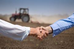 Granjeros shking las manos delante del tractor imagen de archivo