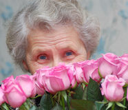 Granny behind bouquet of pink rose Stock Images