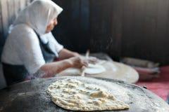 Granny chef cook Turkish pancake Gozleme on the stove Stock Photo
