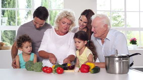 Granny cutting vegetables with the family around Royalty Free Stock Photo