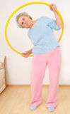 Granny doing gymnastic with hula-hoop. Senior lady doing gymnastic with hula-hoop Royalty Free Stock Images