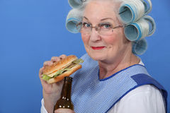 Granny eating a burger. And drinking a beer Stock Images