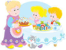 Granny and grandchildren celebrate Easter. Grandmother with her granddaughter and grandson celebrating Easter at the holiday table with a fancy cake and Royalty Free Stock Photo