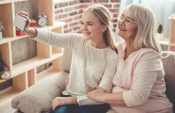 Granny and granddaughter. Beautiful granny and her granddaughter are doing selfie using a smart phone and smiling while sitting on couch at home royalty free stock photo