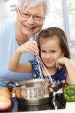Granny and granddaughter cooking smiling Stock Photography