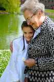 Granny with granddaughter. Grandmother hugging her granddaughter affectionately Royalty Free Stock Photos
