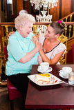Granny and granddaughter laughing in cafe. Senior women and granddaughter laughing having fun with coffee and cake in cafe Stock Images