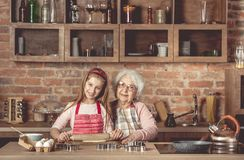 Granny with granddaughter roll out the dough Stock Images