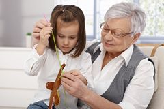 Granny and granddaughter sewing Stock Photography