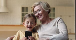 Granny and granddaughter sitting on couch having fun using smartphone