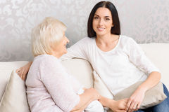 Granny and granddaughter sitting together on couch Royalty Free Stock Photography