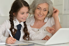 Granny with granddaughter using laptop Stock Photos