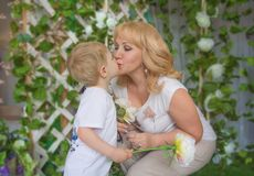 Granny grandson, both blonde kisses, cuddling and kissing. Royalty Free Stock Images