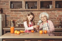 Granny with granddaughter tasting orange juice at kitchen. Granny with happy granddaughter tasting and drinking fresh natural orange juice at kitchen at home royalty free stock photo