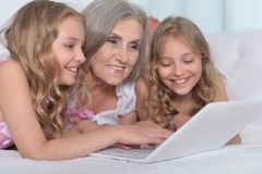 Granny with granddaughters using laptop Stock Images