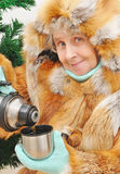Granny with hot tea. Smiling granny with hot tea under fir Stock Photography