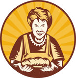 Granny housewife loaf bread. Illustration of an old woman presenting a freshly baked loaf of bread set inside a circle Stock Photos