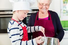 Granny and little boy preparing food in kitchen Royalty Free Stock Images