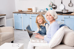 Granny and little girl using laptop Stock Images