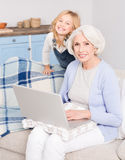 Granny and little girl using laptop. Granny using laptop at home. Mature women with blond hair sitting on sofa or couch and typing on computer. Lady working or Royalty Free Stock Photo