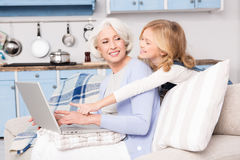 Granny and little girl using laptop Stock Photo