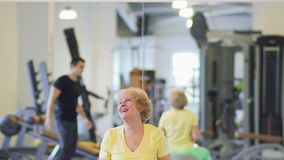 Granny makes exercise with barbell in the gym. Elderly woman makes sport exercises with dumbbells in the gym. She sits on fitness ball and training her arm stock footage