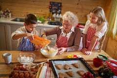 Granny making Christmas cookies with kids Stock Images