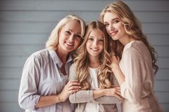 Granny, mom and daughter. Beautiful women generation: granny, mom and daughter are hugging, looking at camera and smiling stock photo
