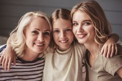 Granny, mom and daughter. Beautiful women generation: granny, mom and daughter are hugging, looking at camera and smiling while sitting on couch at home royalty free stock image